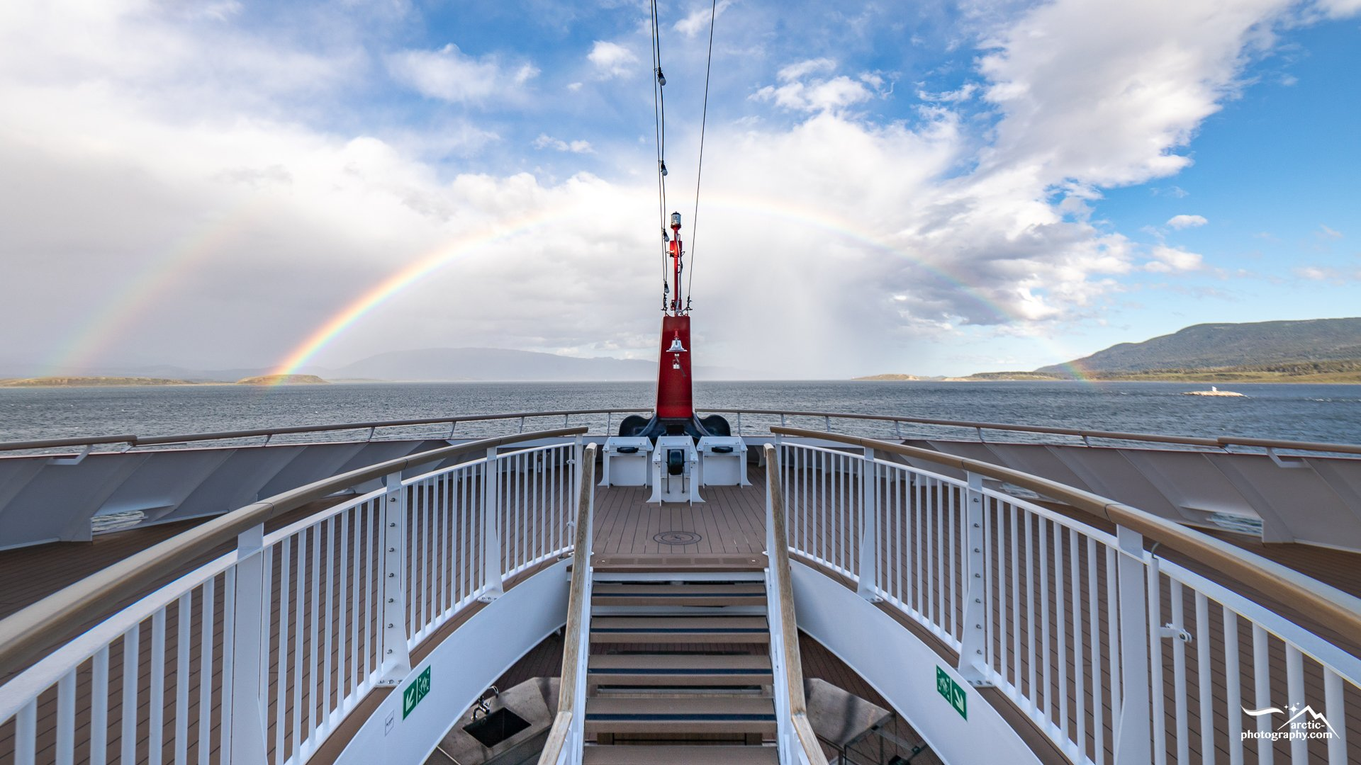 MS Roald Amundsen`s bow with Rainbow leaving the Beagle Canal I Chile